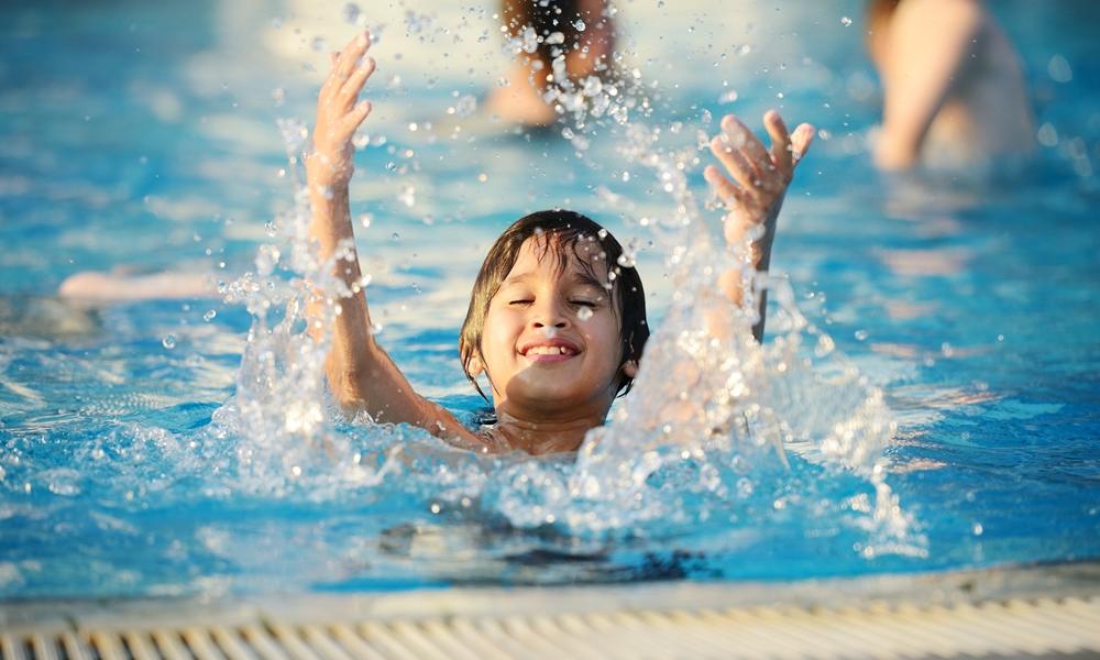 A kid enjoying at a pool