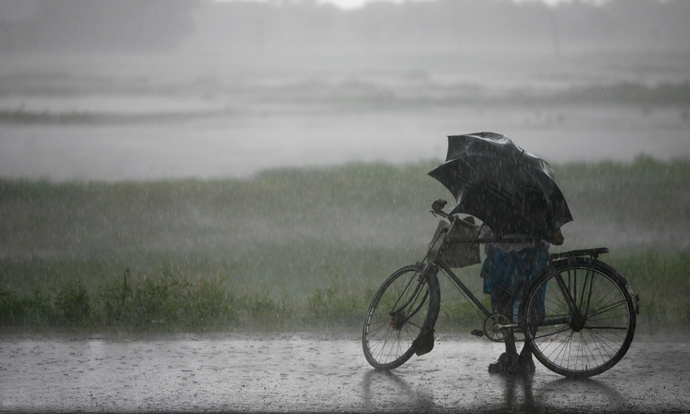 A man on a cycle under an umbrella as it rains in Kerala