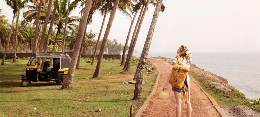 A woman enjoying fresh breeze at a Kerala beach