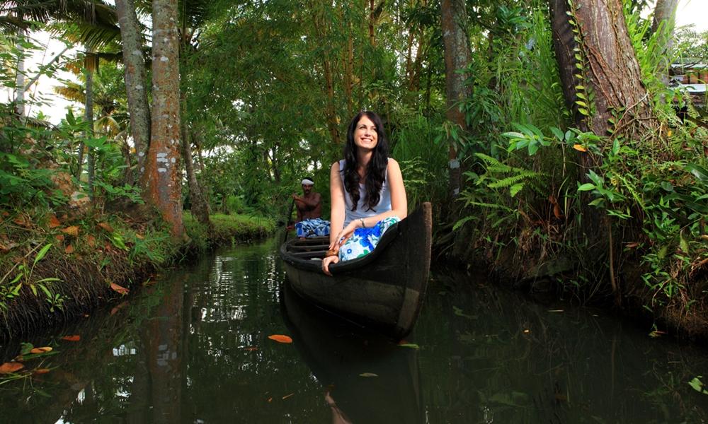 Tourist girl enjoying the beaty of the backwaters on a canoe ride