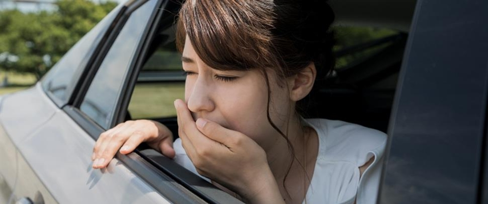 A woman feeling nausea while traveling by car