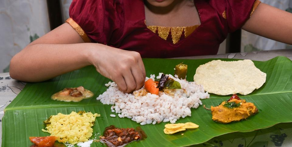 A girl eating Sadhya with her hand