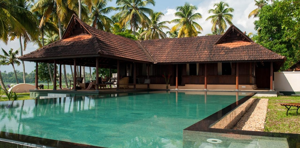 The wooden cottage and pool at Vismaya