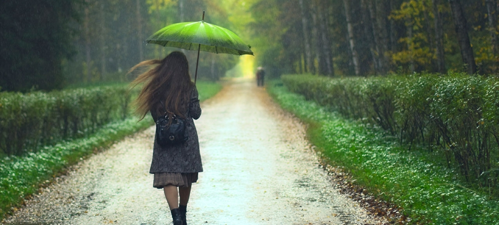 Girl in raincoat walking in the rain