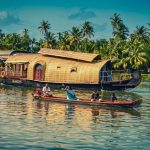 Kerala houseboat passing a canoe in its cruise