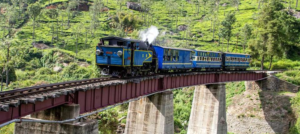 A blue train on a bridge with amazing views all around