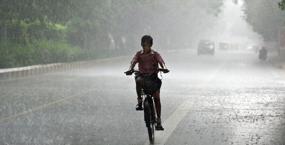 A boy riding his bicycle in the rain