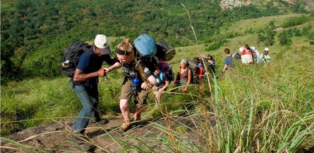 Guided helping a trekker on a difficult trek