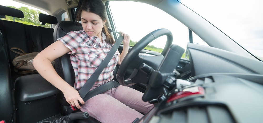 Woman wearing seat belt before starting the car