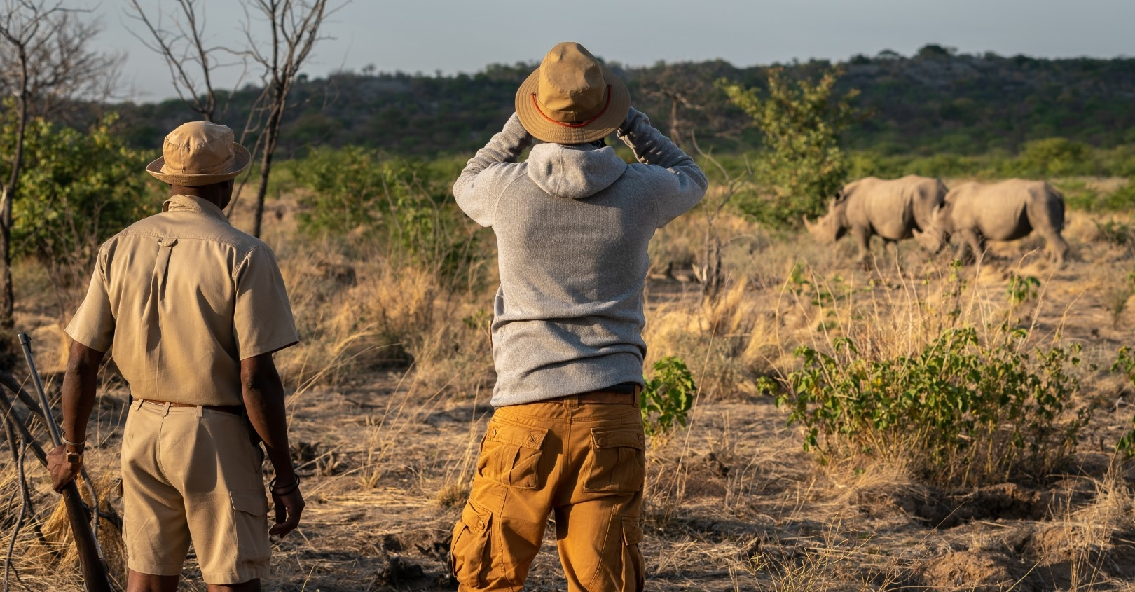 Guide with a gun as a traveler watches rhinoceros