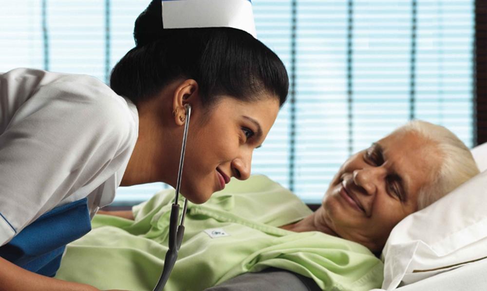 Kerala nurse checking BP of an elderly patient